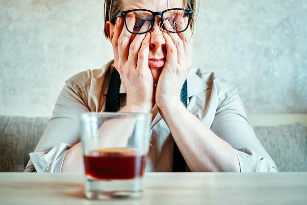 Un homme à lunettes avec un verre de whisky se frotte les yeux.