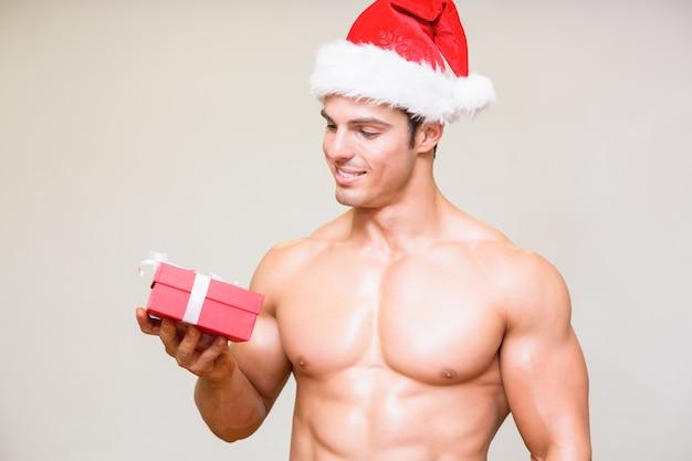 Homme macho en bonnet de noel tenant cadeau sur fond blanc