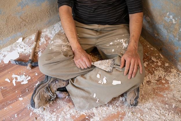 Homme maçon se reposer après avoir enlevé la peinture