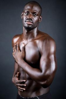 Homme magnifique et musclé en fond sombre.