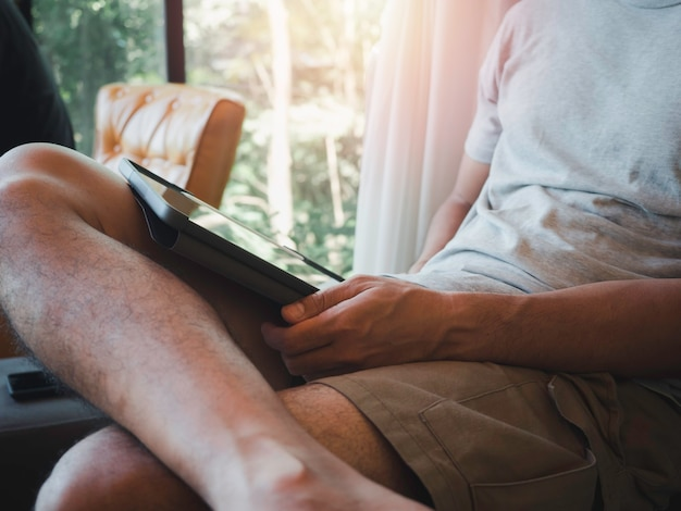 Homme de main à l'aide de tablette numérique. un jeune, un homme en chemise grise décontractée et un short assis et interagissant avec la technologie à la maison. homme d'affaires de relaxation travaillant en ligne à n'importe quel concept.