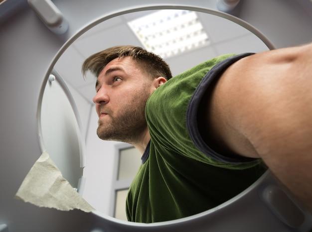 Homme avec la main dans les toilettes