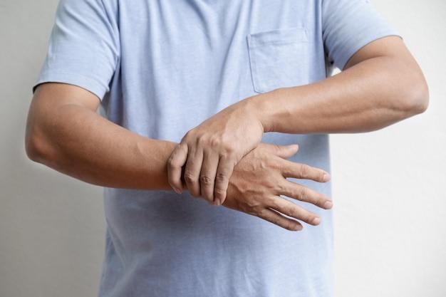 Homme main endolorie et engourdie, picotements épuisés, effet secondaire du syndrome de guillainbarre du vaccin covid