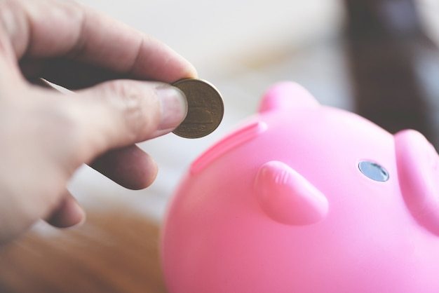 Homme de main mettant de l'argent dans la tirelire à table à la maison se bouchent. économiser de l'argent pour le concept de bourses