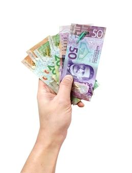 Homme main tenant les billets de nouvelle-zélande sur blanc