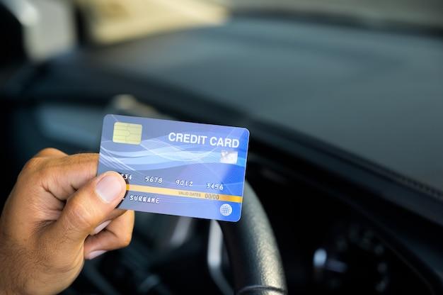 Homme de main tenant une carte de crédit à l'intérieur de la voiture. cette photo concerne le shopping. dépenses d'argent liées aux factures de voiture par carte de crédit