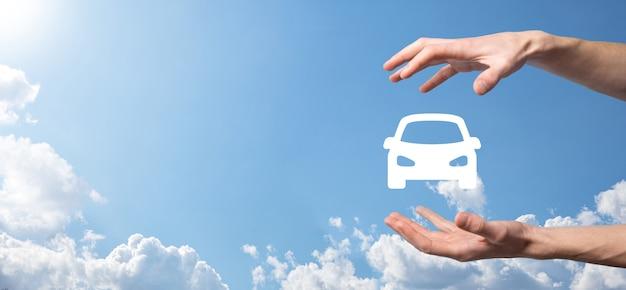 Homme main tenant l'icône auto voiture sur fond bleu. composition de la bannière large. assurance automobile automobile