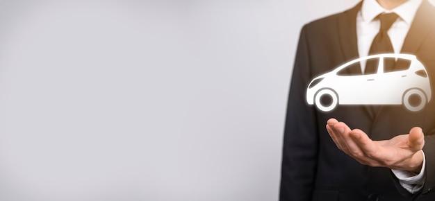 Homme main tenant l'icône auto voiture sur fond gris. composition de la bannière large. concepts d'assurance automobile et d'assurance-collision