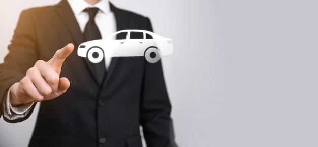 Homme Main Tenant L'icône Auto Voiture Sur Fond Gris. Composition De La Bannière Large. Concepts D'assurance Automobile Et D'assurance-collision Photo Premium