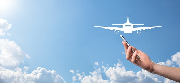 Homme main tenant l'icône d'avion avion sur fond bleu. achat de billets banner.nline. icônes de voyage sur la planification de voyage, le transport, l'hôtel, le vol et le passeport. concept de réservation de billets d'avion.