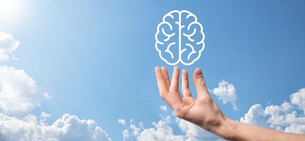 Homme main tenant l'icône du cerveau sur fond bleu. intelligence artificielle machine learning business internet technology concept.banner with copy space.