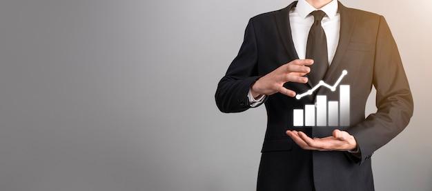 Homme main tenant l'icône du graphique neon.checking analysant le graphique du graphique de croissance des données de vente et le marché boursier sur les réseaux mondiaux. stratégie d'entreprise, planification et marketing numérique