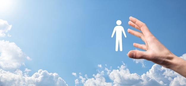 Homme main tenant l'icône humaine sur fond bleu. ressources humaines gestion des ressources humaines recrutement emploi concept de chasse de tête. sélectionnez le concept de chef d'équipe. cliquez sur la main masculine sur l'icône de l'homme. bannière, copiez le spase.