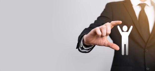Homme main tenant l'icône humaine sur fond gris. ressources humaines gestion des ressources humaines recrutement emploi concept de chasse de tête. sélectionnez le concept de chef d'équipe. cliquez sur la main masculine sur l'icône de l'homme. bannière, copiez le spase.