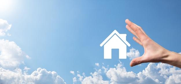 Homme main tenant l'icône de la maison sur fond bleu. concept d'assurance et de sécurité des biens. concept immobilier. bannière avec espace de copie.