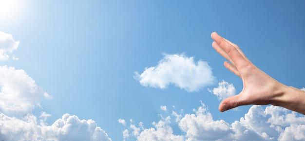 Homme main tenant l'icône de la maison sur fond bleu. concept d'assurance et de sécurité des biens. concept immobilier. conditions météorologiques, nébulosité. bannière avec espace de copie.
