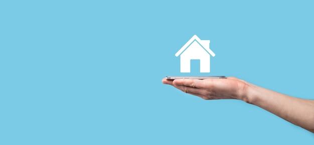 Homme main tenant l'icône de la maison sur fond bleu. concept d'assurance et de sécurité des biens. concept immobilier.