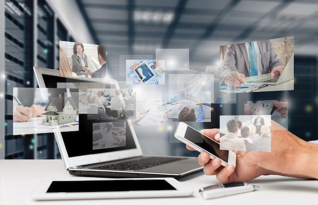 Homme main tenant un smartphone assis à table près d'un ordinateur portable avec des hologrammes numériques