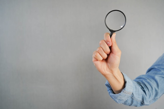 Homme main tenir loupe pour la recherche d'informations