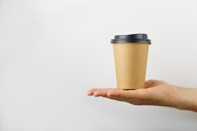 Homme main tient sur sa paume une tasse de papier café à emporter isolé sur fond blanc