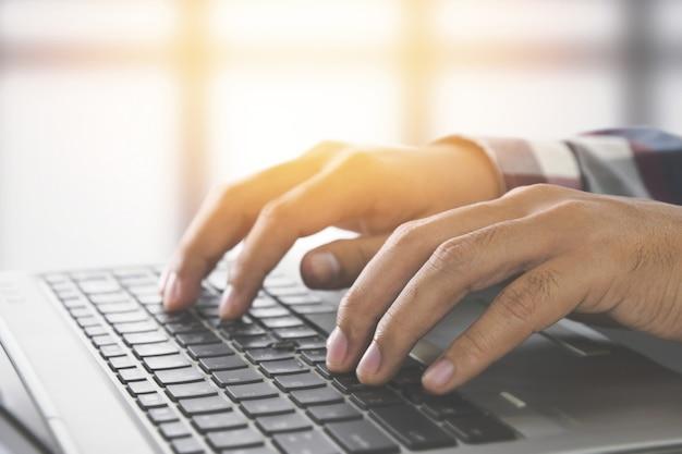 Homme, mains, dactylographie, clavier portable, bureau, développeur, site web