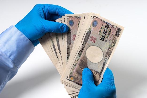 Homme, mains, dans, bleu, nitrile, gant, tenue, billets banque