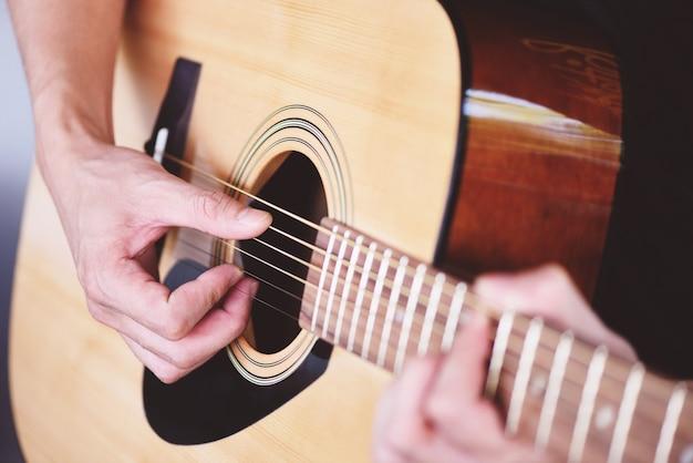 Homme mains jouant de la guitare acoustique, gros plan guitariste instrument de musique