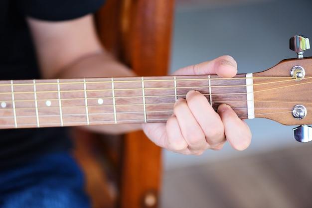 Homme mains jouant de la guitare acoustique, gros plan joueur de guitare instrument de musique passe-temps à la maison