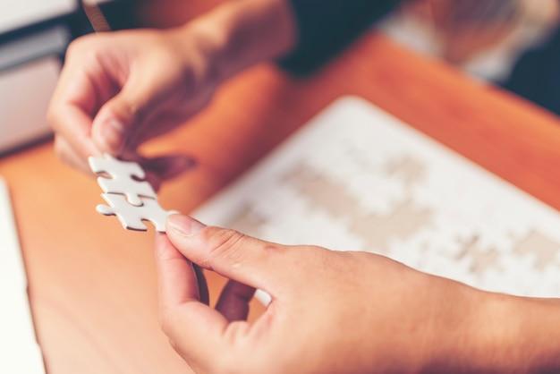 Homme mains reliant couple pièce de puzzle dans le bureau. entreprise réussie