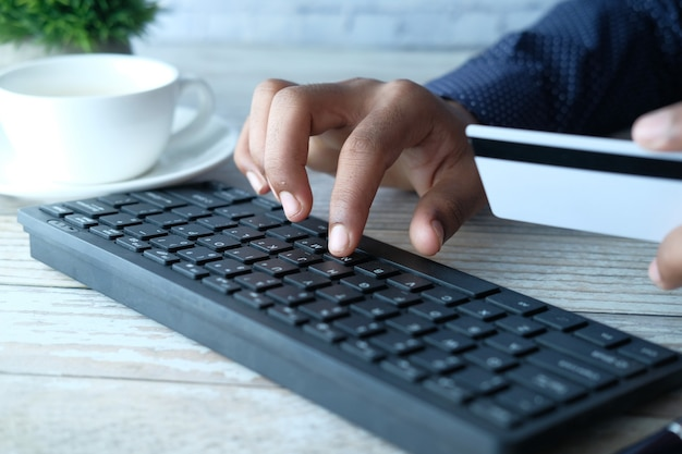 Homme, mains, tenue, carte crédit, et, utilisation ordinateur portable, achats en ligne