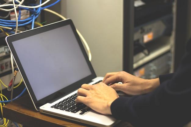 Homme de mains utilisant un ordinateur portable pour vérifier les serveurs du centre de données