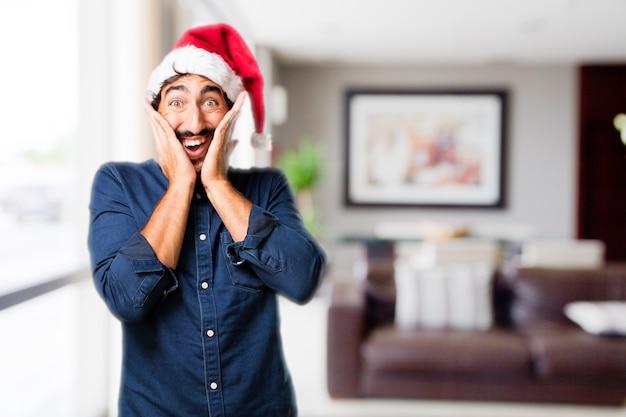 L'homme avec les mains sur le visage et le chapeau de santa
