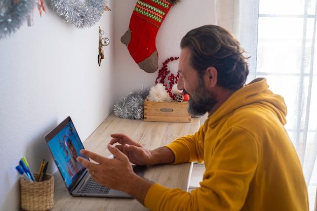 Un homme à la maison appelle une femme pour célébrer la veille de noël avec une conférence par vidéoconférence. les gens utilisent un ordinateur portable et une connexion internet pour appeler des amis ou une femme par vidéo