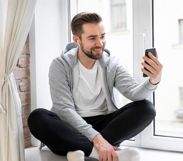 Homme à la maison ayant un appel vidéo avec la famille