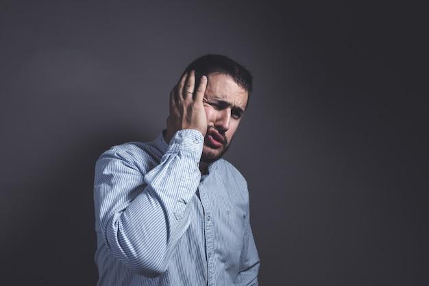 Homme avec un mal de dents met sa main