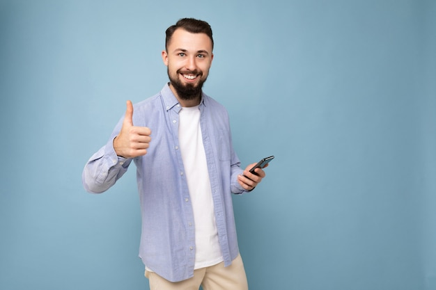 Homme mal rasé avec barbe portant un t-shirt blanc élégant et une chemise bleue