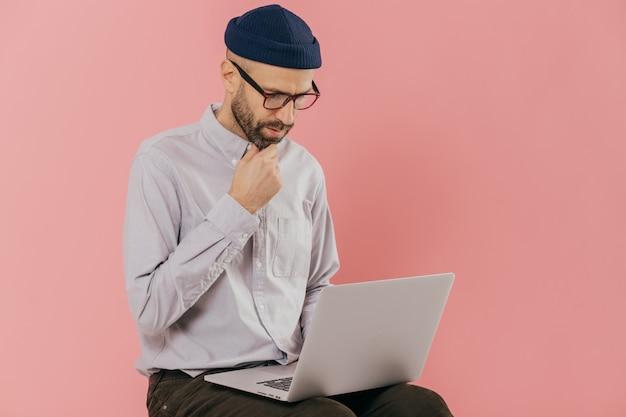 Un homme mal rasé concentré tient le menton et regarde attentivement l'écran d'un ordinateur portable