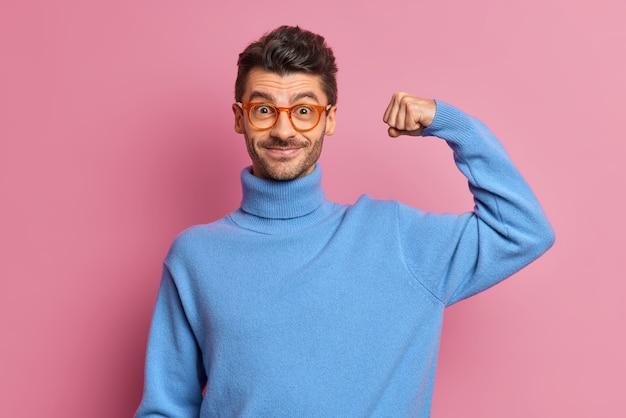 Un homme mal rasé gai et confiant lève le bras et montre que les muscles ressentent de la puissance