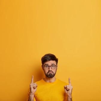 Un homme mal rasé mécontent porte les lèvres, a l'air malheureux, se sent insulté, montre un espace de copie pour la promotion d'un produit ou d'un service, insatisfait de l'absence de rabais en magasin, pose sur un mur jaune