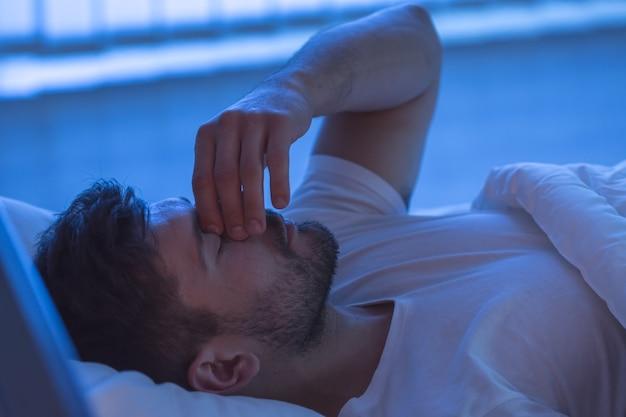 L'homme avec un mal de tête dormant sur le lit. la nuit