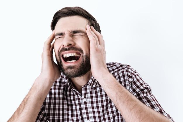 Un homme a mal à la tête. il garde les mains sur la tête.