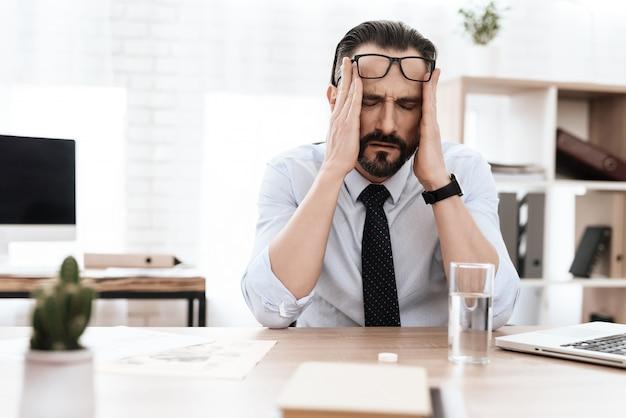 Un homme a mal à la tête.