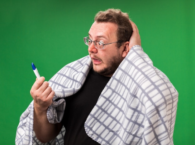 Un homme malade d'âge moyen effrayé enveloppé dans un plaid tenant un thermomètre saisi la tête
