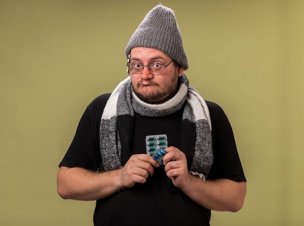 Homme malade d'âge moyen impressionné portant un chapeau d'hiver et une écharpe tenant des pilules isolées sur un mur vert olive