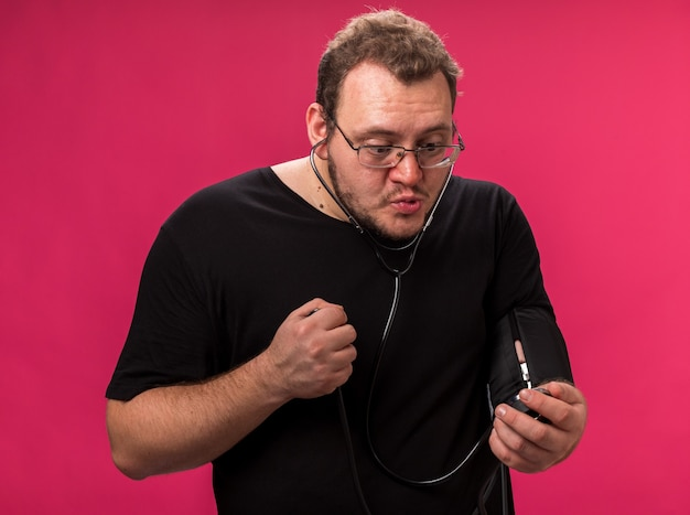 Homme malade d'âge moyen mécontent mesurant sa propre pression avec un sphygmomanomètre