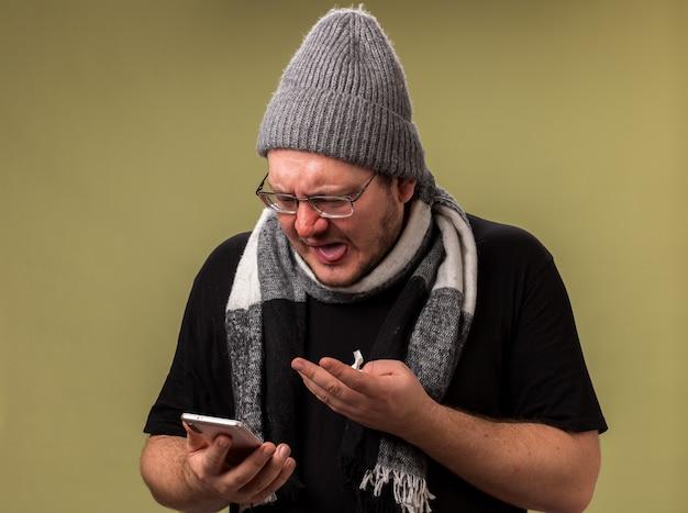 Homme malade d'âge moyen mécontent portant un chapeau d'hiver et une écharpe tenant et pointe au téléphone