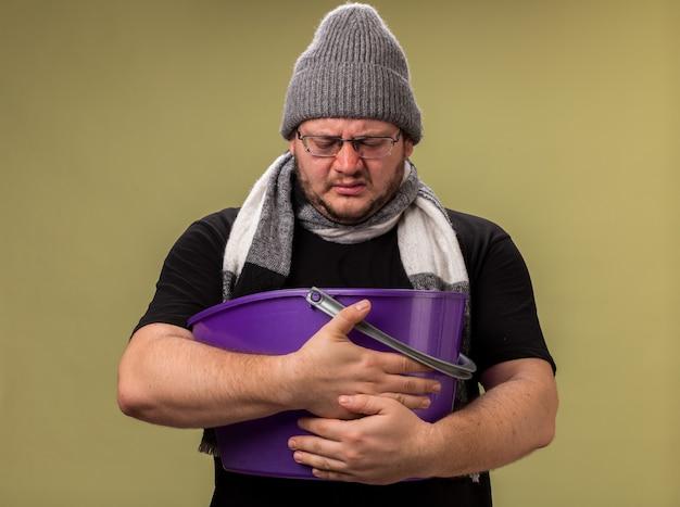 Homme malade d'âge moyen mécontent portant un chapeau d'hiver et une écharpe tenant et regardant un seau en plastique