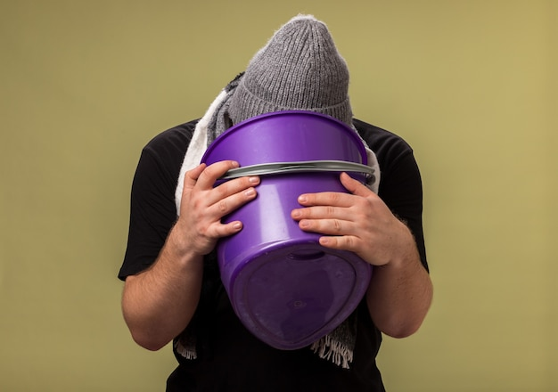 Homme malade d'âge moyen portant un chapeau d'hiver et une écharpe tenant un seau en plastique et vomissant dedans
