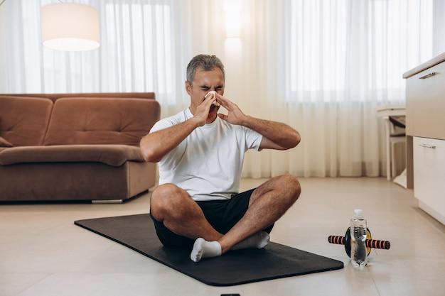 Homme malade âgé avec le nez qui coule assis sur un tapis de yoga noir