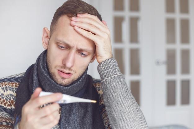 Un homme malade apprend sa température élevée à la maison dans le salon.